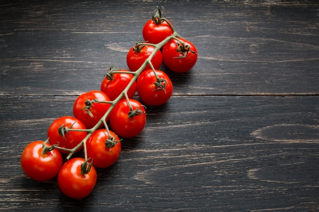 Tomates de cereja vermelhos em um ramo no fundo escuro. comida de dieta saudável