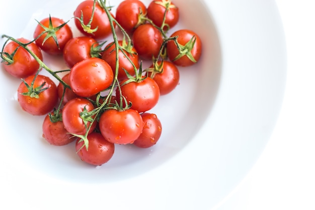 Tomates de cereja vermelhos frescos maduros em um fundo branco