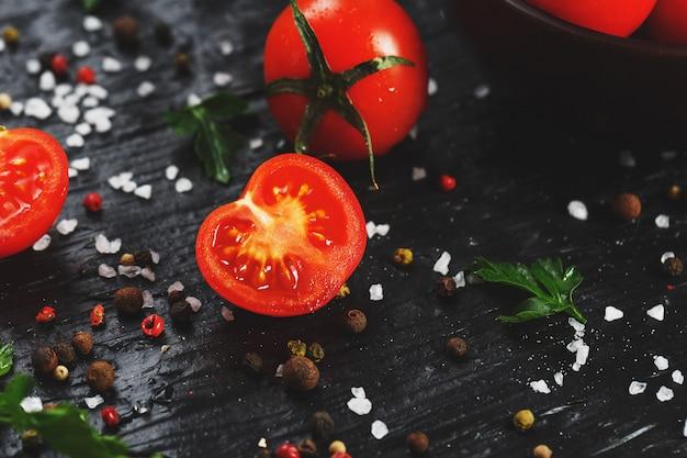 Tomates de cereja vermelhos suculentos com especiarias, sal grosso e verdes. tomates doces e maduros para saladas e como ingredientes para cozinhar