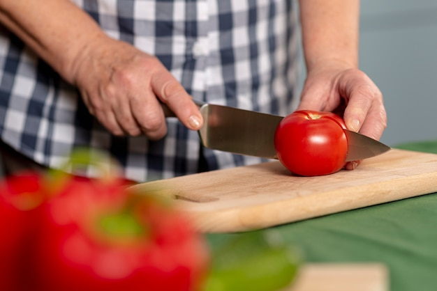 Tomates de corte de mulher mais velha em close-up