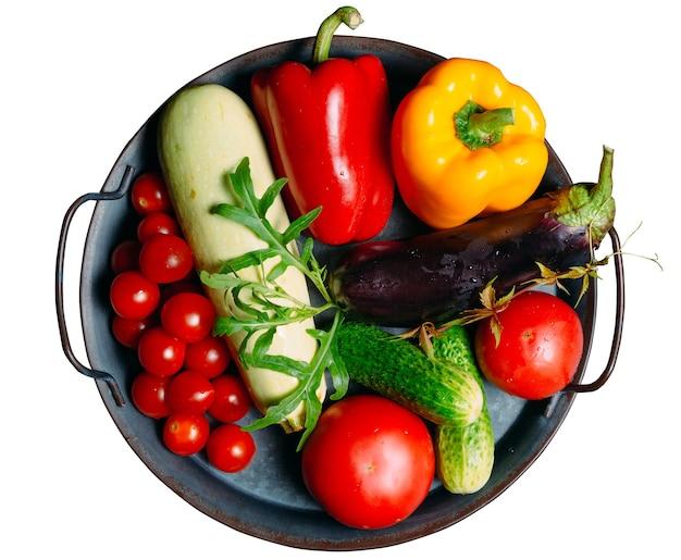 Tomates de legumes frescos, pepinos, pimentões, abobrinhas e berinjela, isolados em um fundo branco.