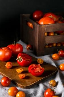 Tomates de outono em ângulo alto na tábua e na caixa