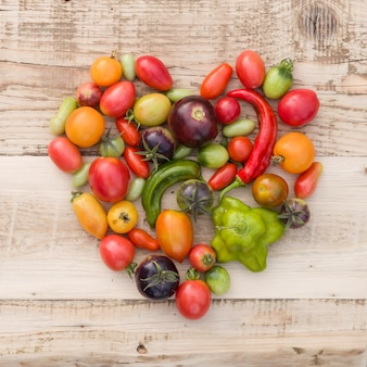 Tomates de vegetais orgânicos coloridos e páprica em forma de um coração no fundo de madeira