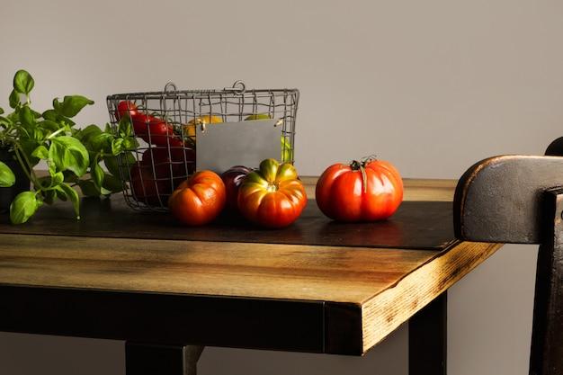 Tomates diferentes em uma cesta de arame e sobre uma mesa de madeira