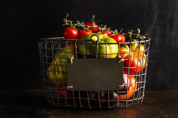 Tomates diferentes em uma cesta de arame em um fundo escuro