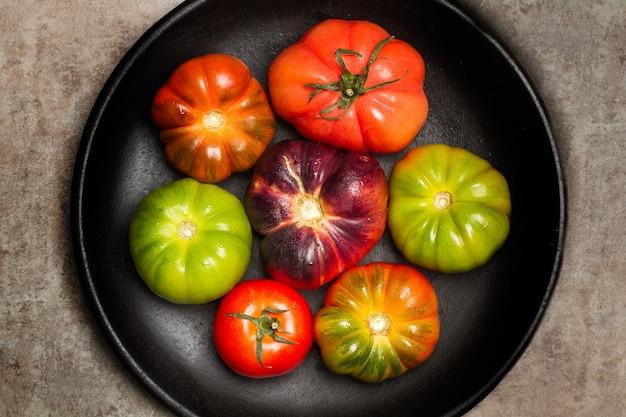 Tomates diferentes em uma placa preta e sobre uma mesa de mármore