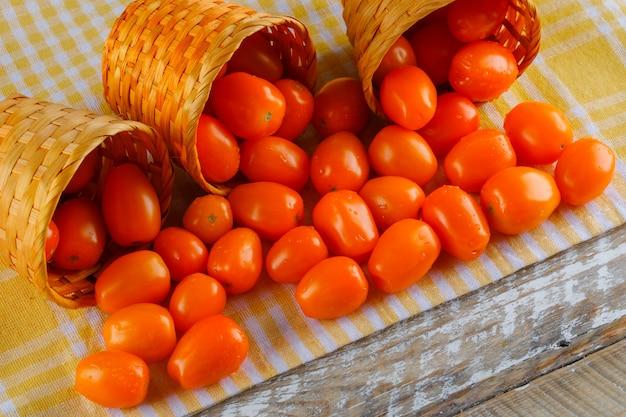 Tomates dispersos da vista de alto ângulo de cestas no pano de piquenique e espaço de madeira