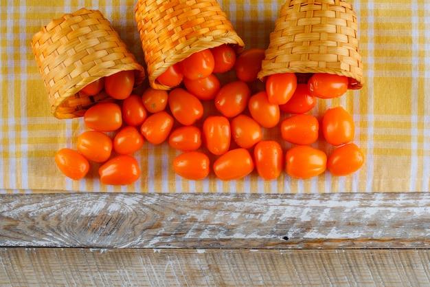 Tomates dispersos de cestas de vime planas colocar no pano de piquenique e espaço de madeira
