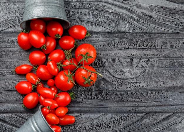 Tomates dispersos de mini baldes em uma parede de madeira cinza. vista do topo.
