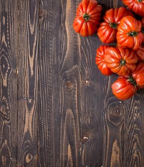 Tomates do coração do boi no espaço livre do fundo de madeira rústico para o texto.