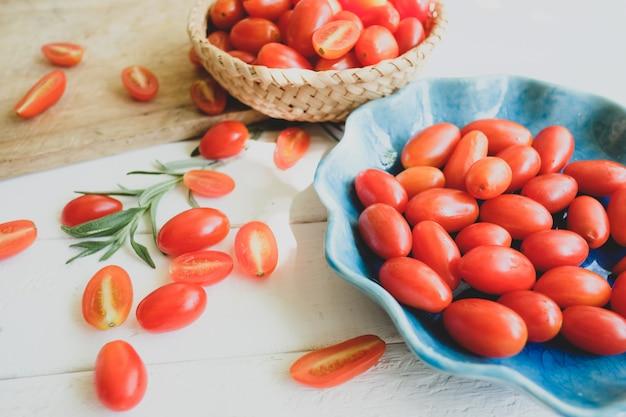 Tomates e alecrins frescos em um fundo branco.