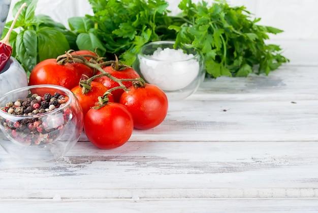 Tomates e bando de manjericão verde fresco sobre um fundo branco de madeira,