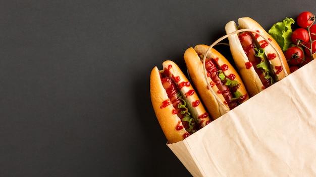 Tomates e cachorros-quentes em saco de plástico