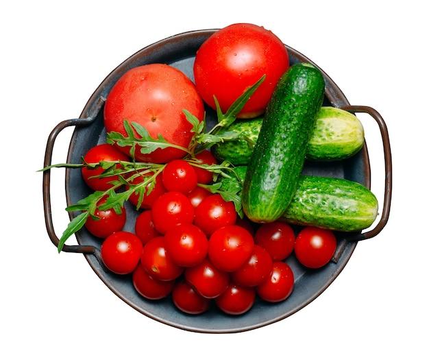 Tomates e pepinos de legumes frescos, isolados em um fundo branco.