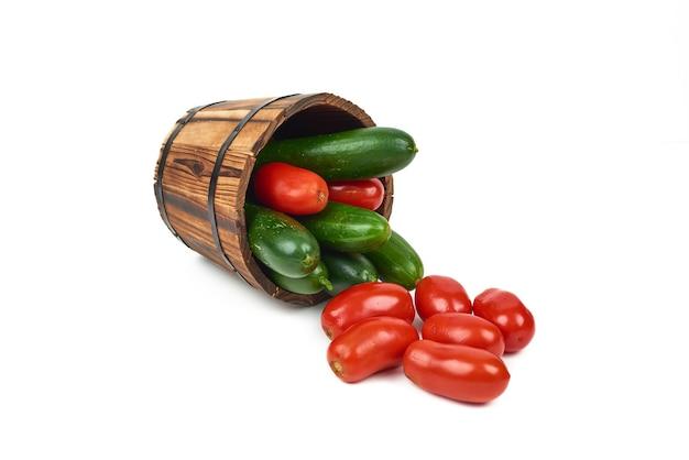 Tomates e pepinos fora de um balde de madeira em branco.