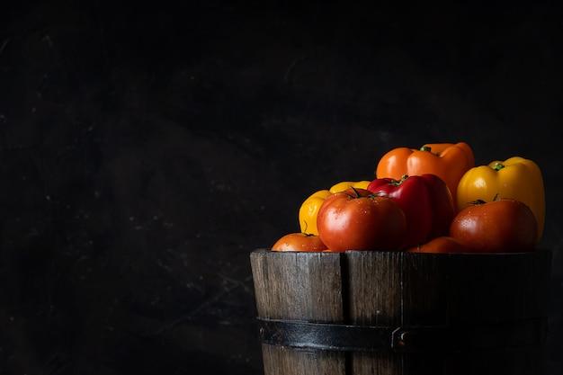 Tomates e pimentões no look vintage de balde de madeira