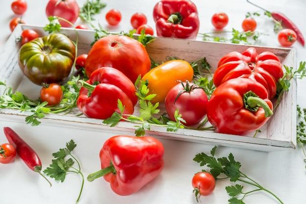 Tomates e pimentos frescos na bandeja de madeira