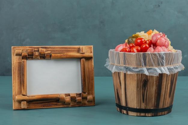 Tomates em conserva, azeitonas, alho, repolho, pepinos em balde de madeira com moldura.