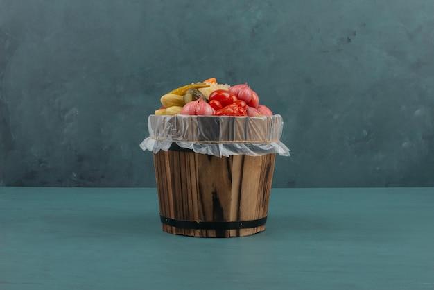 Tomates em conserva, azeitonas, alho, repolho, pepinos em balde de madeira.