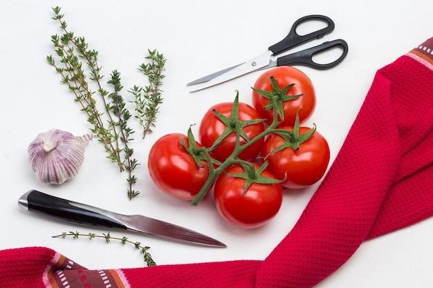 Tomates em galho verde. faca e tesoura. raminhos de alho e tomilho. guardanapo vermelho. fundo branco. postura plana
