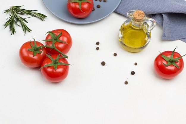 Tomates em galho verde. tomate e pimenta da jamaica no prato cinza. azeite em garrafa. guardanapo cinza. fundo branco. copie o espaço