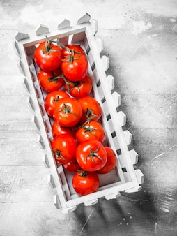 Tomates em uma caixa de plástico na mesa de madeira branca