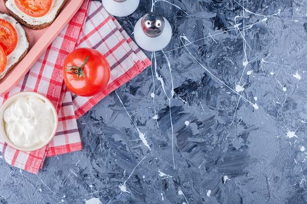 Tomates fatiados em um pão de queijo ao lado de sal em uma toalha, no azul.