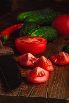 Tomates fatiados na tábua e pepinos com pimenta na mesa de madeira.