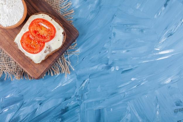 Tomates fatiados no pão de queijo e uma tigela de farinha na tábua no guardanapo de pano azul.