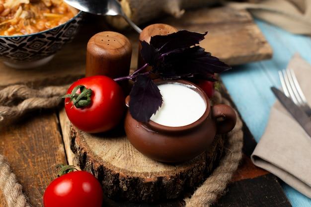 Tomates frescos, basílico e um pote de iogurte na placa de madeira.