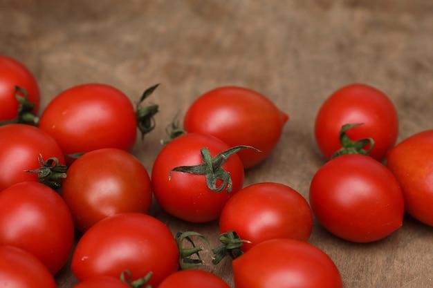 Tomates frescos, brilhantes e suculentos na mesa da cozinha