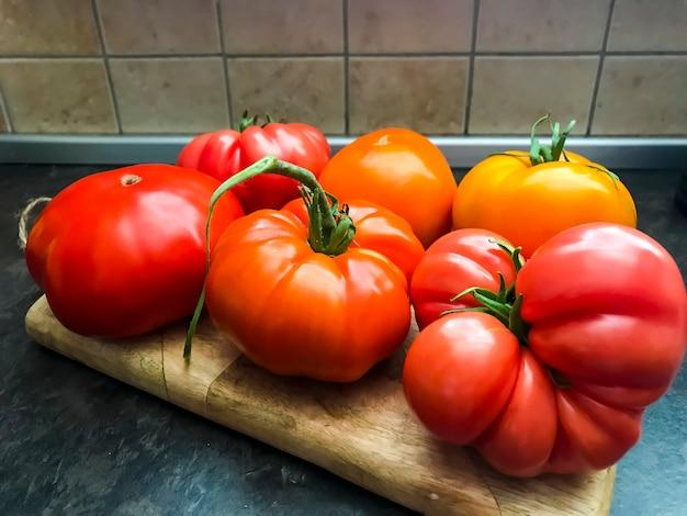 Tomates frescos coloridos na placa de madeira da cozinha.