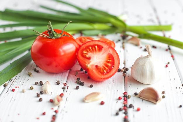Tomates frescos com especiarias. alimento saudável orgânico no alho verde de madeira. legumes de verão e outono.