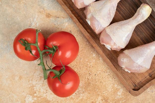 Tomates frescos com tábua de madeira de coxas de frango cru.