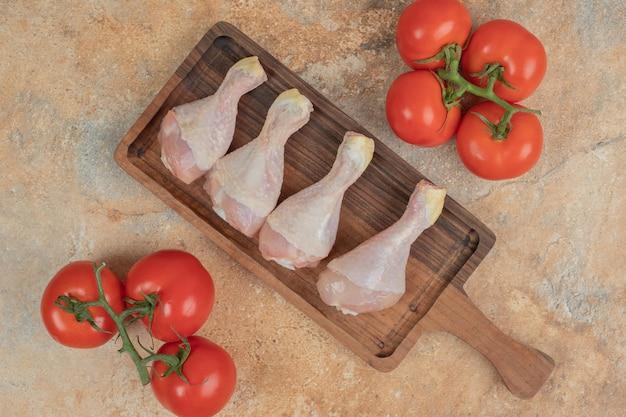 Tomates frescos com tábua de madeira de coxas de frango cru