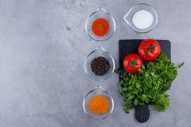 Tomates frescos e folhas de salsa em uma placa de corte preta com condimentos.