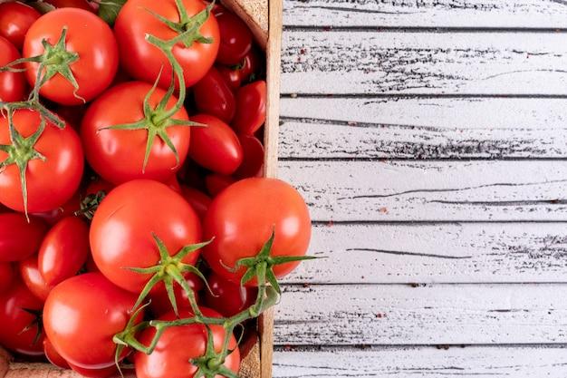 Tomates frescos em caixa de madeira na superfície de madeira branca