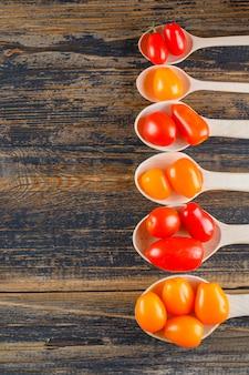 Tomates frescos em colheres de madeira em uma mesa de madeira. configuração plana.