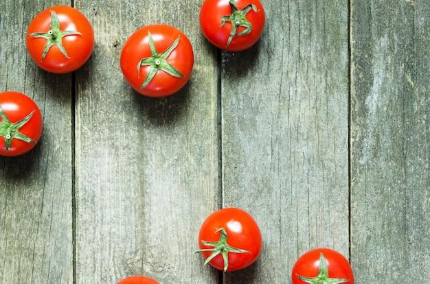 Tomates frescos em fundo de madeira rústica
