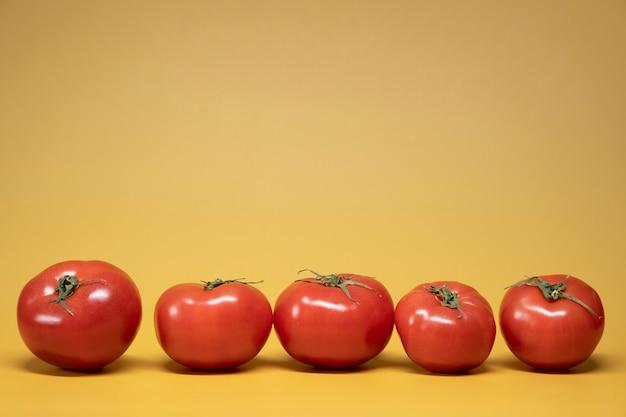 Tomates frescos em um fundo amarelo brilhante em um estilo de foto de comida de publicidade. moldura horizontal