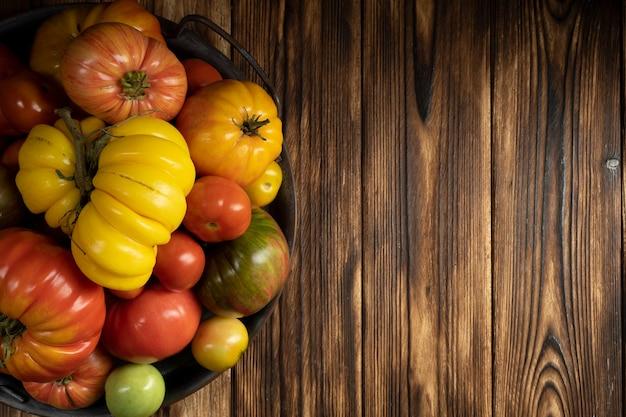 Tomates frescos em um fundo escuro de madeira colheita de tomates