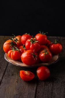 Tomates frescos em um prato em um fundo escuro colhendo tomates