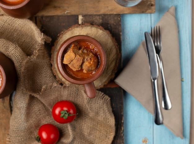 Tomates frescos em uma serapilheira e vasos de piti caucasiano ao redor