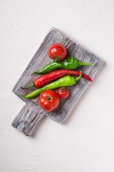 Tomates frescos maduros com pimenta malagueta na velha tábua de madeira, mesa de concreto de pedra branca, vista superior