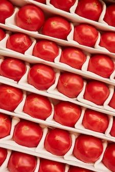 Tomates frescos maduros em fila prontos para venda em estande no mercado de fazendeiros