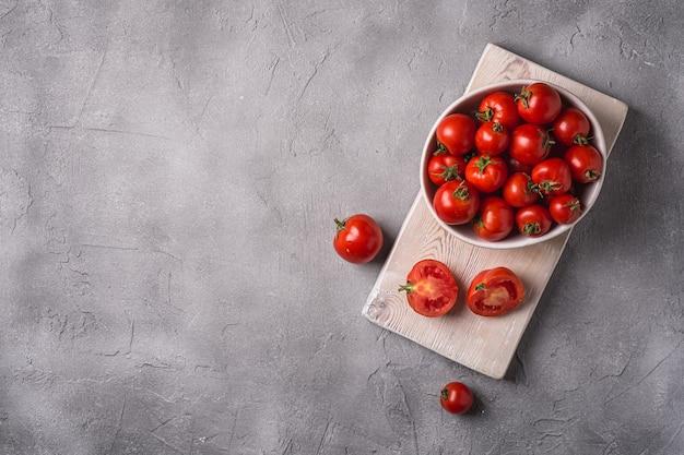 Tomates frescos maduros inteiros e fatiados em uma tigela e na velha tábua de madeira, espaço de cópia de concreto de pedra