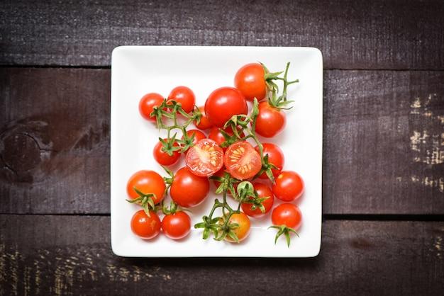 Tomates frescos no prato branco com fundo escuro de madeira