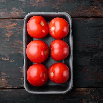 Tomates frescos orgânicos vermelhos, na mesa de madeira escura