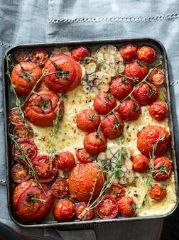 Tomates frescos, queijo feta, alho e tomilho na bandeja