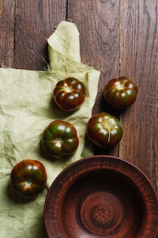 Tomates frescos saborosos no fundo de madeira e pano